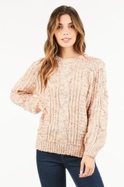 Pastel cable knit sweater features colored speckles throughout.