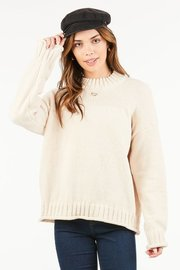 A soft, velvety pullover with raw, rolled hemlines and cable knit bordering.