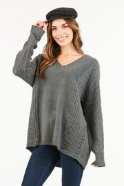 An oversized, knit sweater with a ribbed v shaped neckline and loose long sleeves.