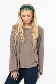An oversize waffle knit top with drop shoulder long sleeves and a high/low hemline.