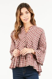 Small tortoise buttons lead their way to a peplum hemline on this wide sleeved print blouse.