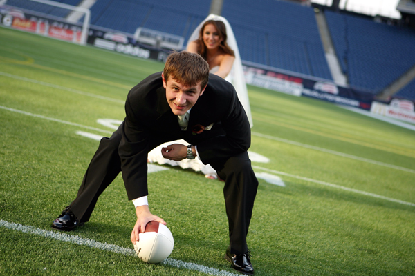 bride and groom playing football in Gillette Stadium wedding photo