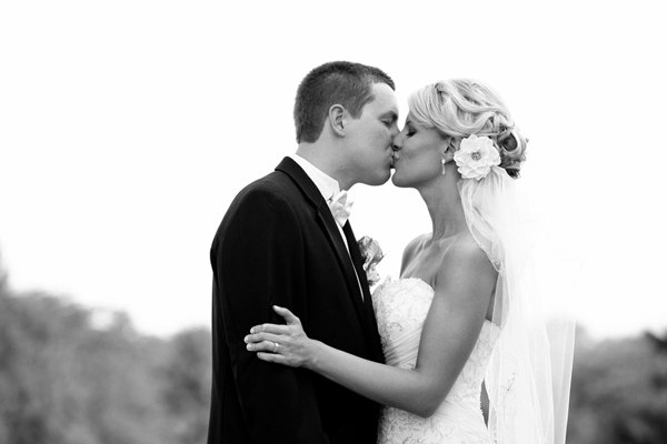bride and groom kiss black and white photo