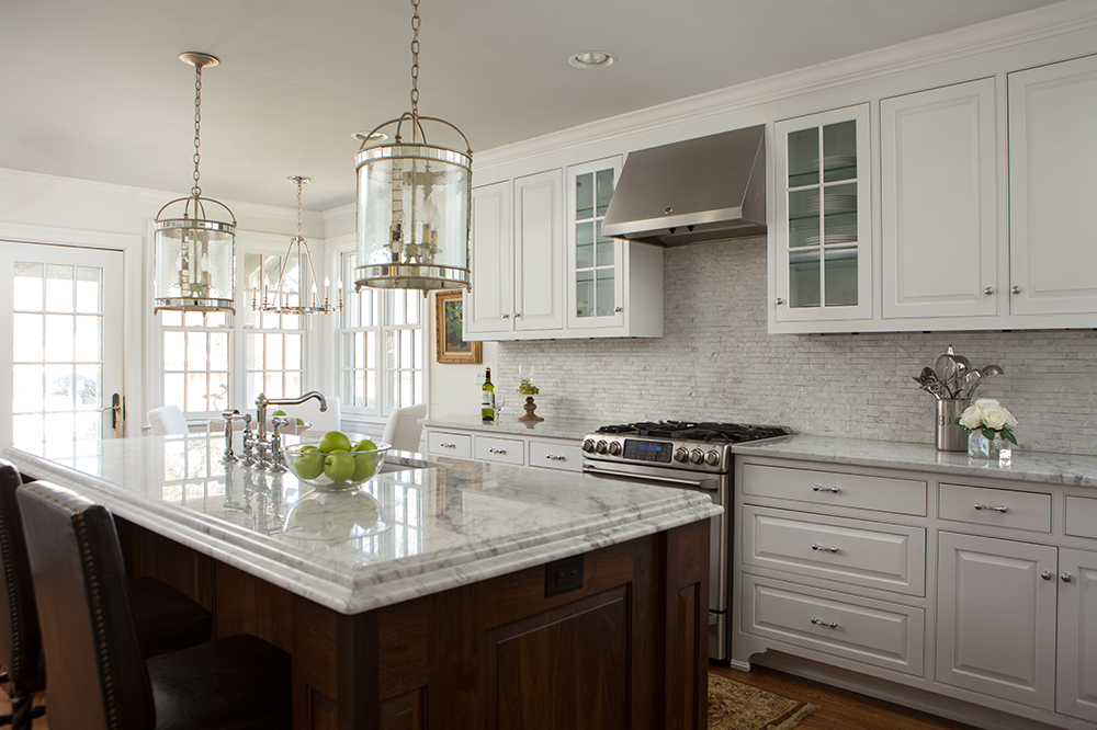 white kitchen cabinets with white marbled backsplash and marble countertops with gold island pendants and stainless steel