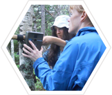 Volunteers checking a camera-trap.