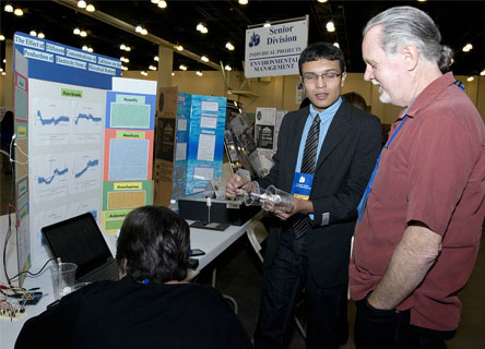 Neel shows off his battery at the Los Angeles County Science Fair.
