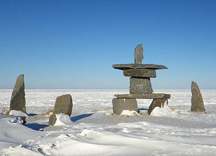 "Canadian Inuit ""inukshuk"" monument and frozen landscape, Churchill, Canada."