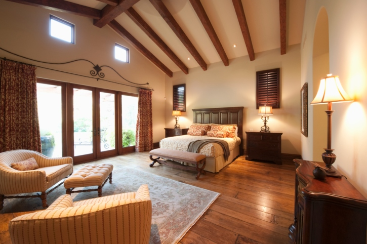 Master bedroom with vaulted ceiling with exposed beams hard wood