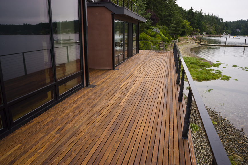 Long narrow deck attached to modern home overlooking water with metal ...