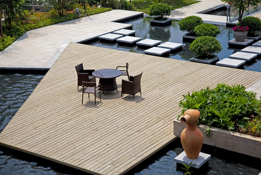 Large wood deck surrounded by pools and gardens for Modern garden decking designs