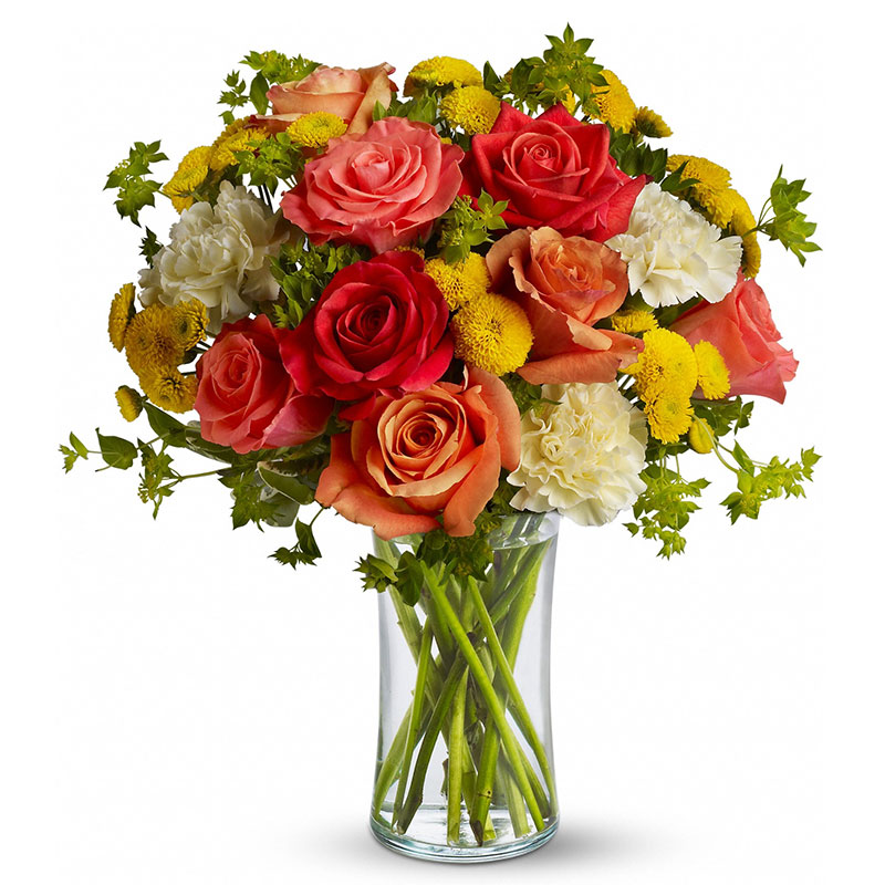 Dark orange, coral and orange roses, light yellow carnations, yellow button spray chrysanthemums and greens fill a slender gathering vase. It's a kiss of summer!