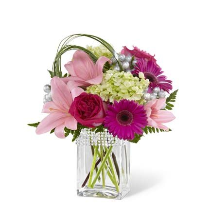 Hot pink roses and gerbera daisies are a standout in this bouquet surrounded by pale pink Asiatic Lilies and the alluring texture of green mini hydrangea blooms perfectly accented with bear grass blades and lush greens to create a simply stunning flower arrangement. Presented in a clear glass vase with silver beading lined at the top, this mixed flower bouquet is that perfect expression of love and kindness to send in honor of a birthday, as a way to express your thanks and gratitude, or in celebration of an anniversary.