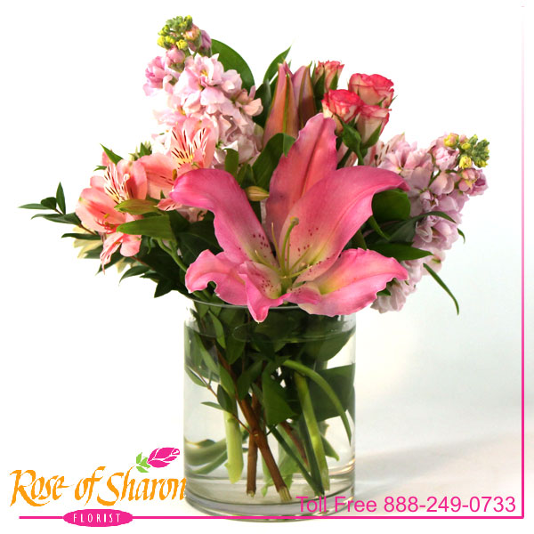 Spring Touch is an arrangement of Oriental Lily, fragrant stock, alstromeria and miniature rose buds in a glass cylinder.