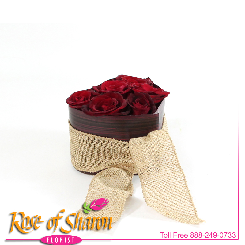 A heart of six open roses, wrapped with faux foliage and jute ribbon and adorned with a perfect orchid bloom.