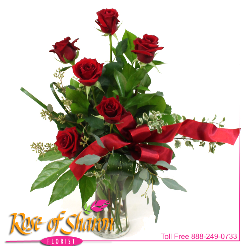 Six royal roses stand vibrantly in a vase of assorted greenery ready to convey your affections.