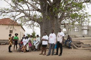 Church members and community health activists gather beneath a baobob tree.