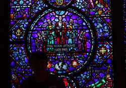 A woman stands silhlouetted against a stained-glass window outside the Uppler Room chapel, which draws thousands of visitors each year.