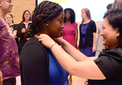 Kathleen Pryor (left) receives the anchor cross from Judy Chung as 29 young adult missionaries were commissioned and sent into service by the General Board of Global Ministries in August 2013.