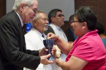 The Rev. Noé Gonzales (left) offers Holy Communion to Nohemi Ramirez during opening worship at the 2011 MARCHA meeting at the Lydia Patterson Institute in El Paso, Texas. Photo by Mike DuBose, UMNS.