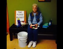 Florence Millard sitting with cleaning buckets for UMCOR. Photo courtesy UMCOR.