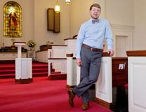 The Rev. Tyler Hege, 23, stands in the sanctuary of Shiloh United Methodist Church where he has served as associate pastor and youth pastor. Hege has now become the pastor at two churches, Bethel United Methodist in King and Mount Olivet United Methodist in Walkertown. Photo by Donnie Roberts, The Dispatch.