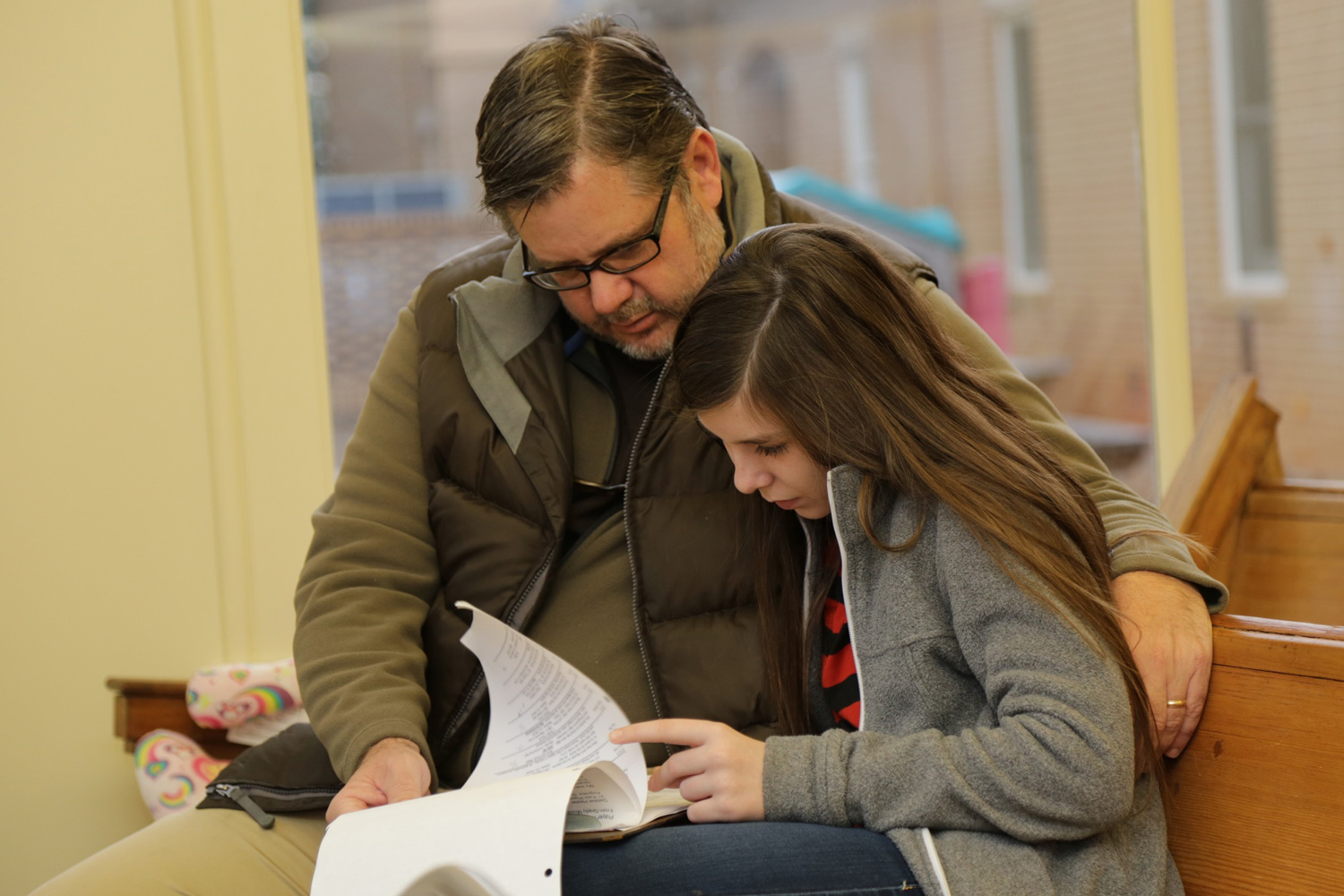 A father and daughter share time together while serving a prayer ministry.