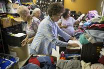 Elizabeth Jimenez (foreground) helps sort donated clothing for recent immigrants from Central America in the welcome center at the Holding Institute in Laredo, Texas. Jimenez was a student in the boarding school at Holding, a United Methodist Women National Mission Institution. She is flanked by, from left: Rosa Maria Narvaez, Lydia Mejorado and Elva Guzman. The volunteers are from La Trinidad United Methodist Church in Laredo. Photo by Mike DuBose, UMNS.; Mike DuBose, UMNS