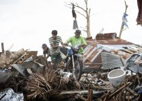 Men remove a motorcycle from storm debris piled up by Typhoon Haiyan in Tacloban, Philippines. A UMNS photo by Mike DuBose.; A UMNS photo by Mike DuBose