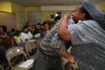 Sheri Tyler Kimble shares a hug with Sean Siple during the giving of peace. Photo by Kathleen Barry, UMNS.