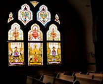 Beautiful stained-glass windows cast shadows on pews inside Grace United Methodist Church in New Orleans, La. Photo by Kathy L. Gilbert.