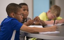 Scholars (from left) William, Jermaine and Larry bear down on a writing assignment at the Gordon Memorial Freedom School in Nashville, Tenn. Photo by Mike DuBose, UMNS.