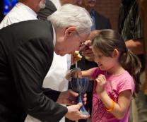 The Rev. Noé Gonzales (left) offers Holy Communion to Kaylee Naomi Avita Guerrero. Photo by Mike DuBose, UMNS.