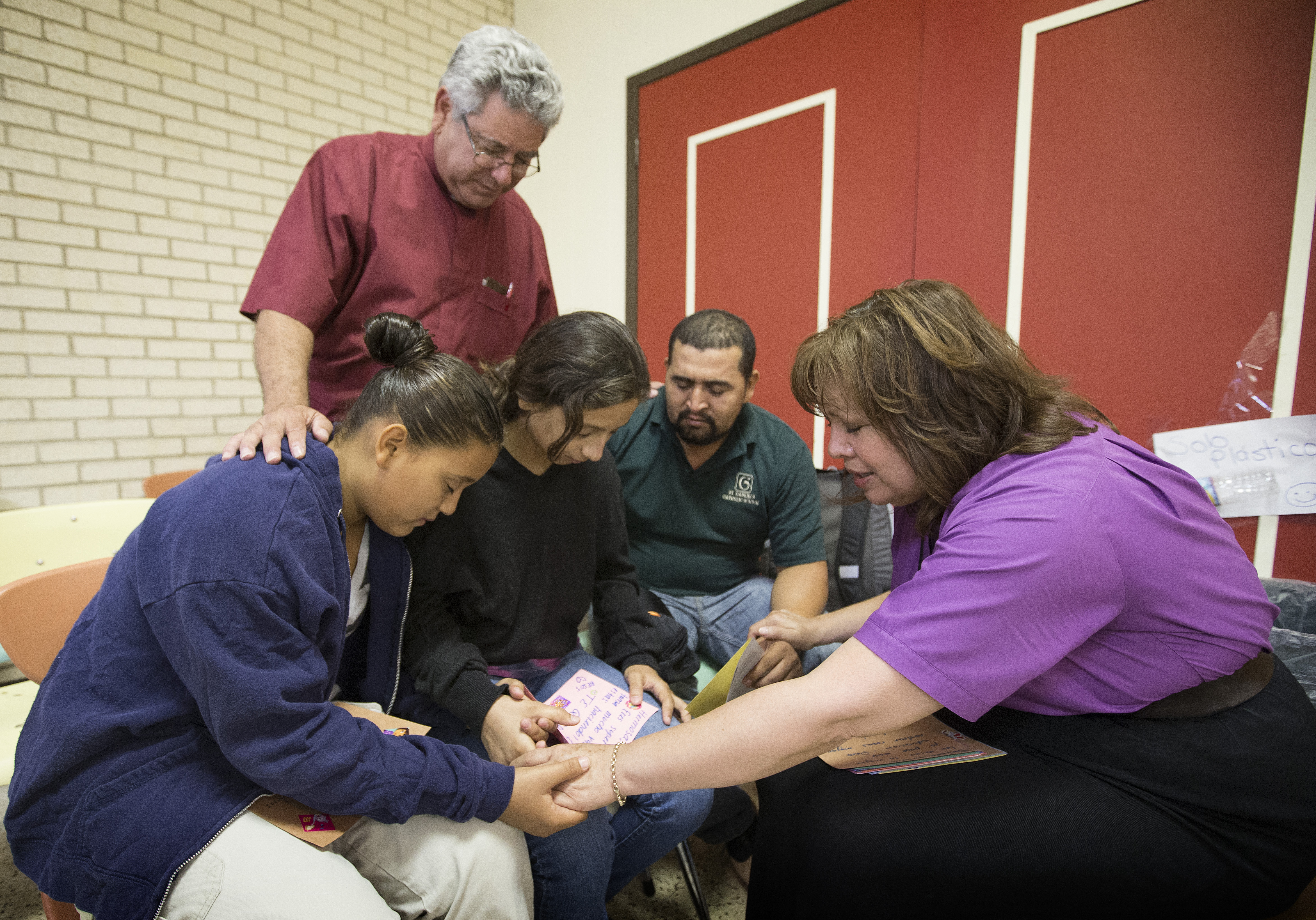United Methodist Bishop Minerva Carcaño (right) and the Rev. Javier Leyva (standing) pray with Elmer Moreno Gonsales and his daughters Mariela (left) and Katerin at the immigrant welcome center at Sacred Heart Catholic Church in McAllen, Texas. The family immigrated from Honduras following a month-long journey. File photo by Mike DuBose, UMNS