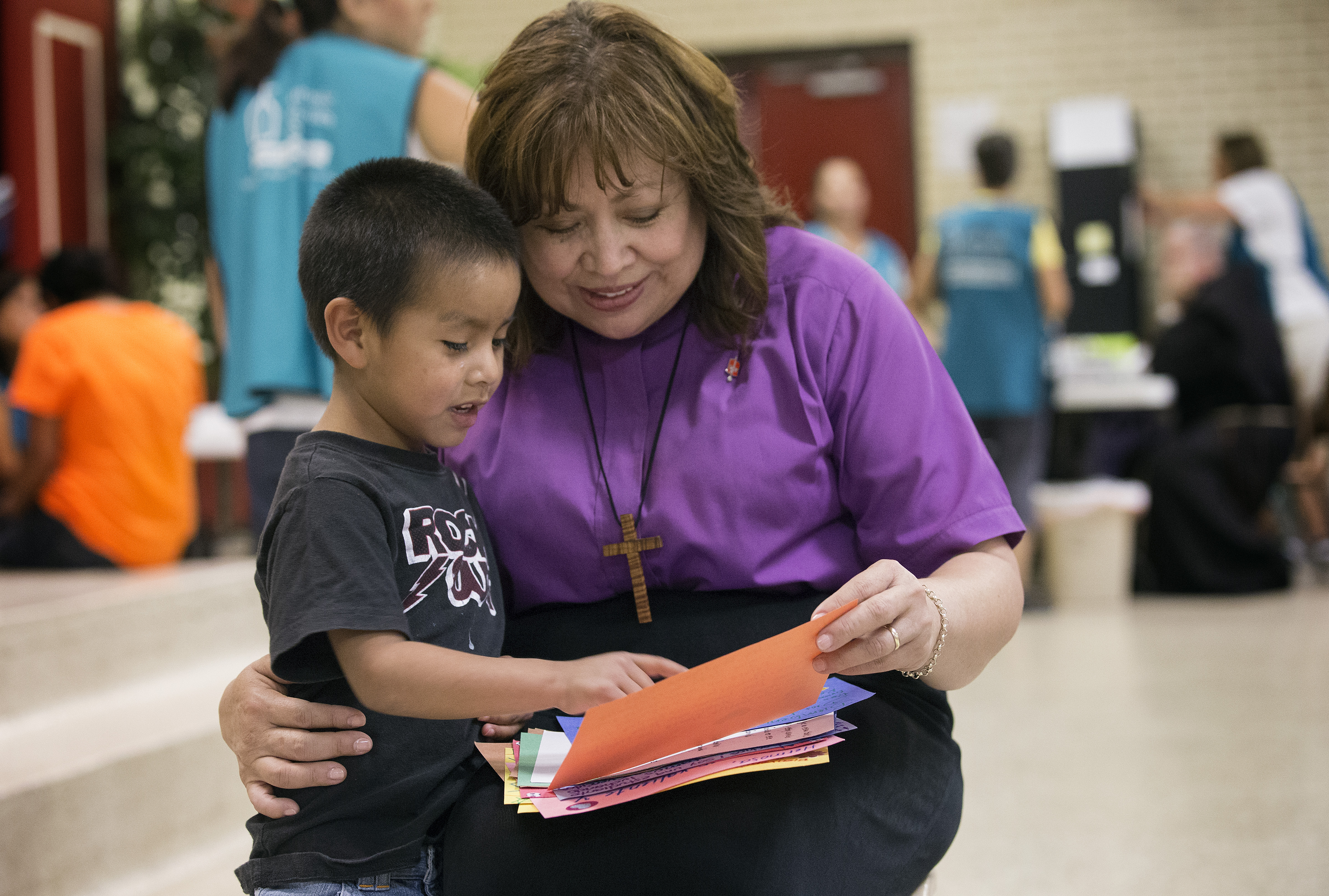 United Methodist Bishop Minerva Carcaño (right) shares letters of encouragement with Regino Enrique at the immigrant welcome center at Sacred Heart Catholic Church in McAllen, Texas, in August 2014. The 5-year-old and his mother, Macaria, arrived from Guatemala after a month-long journey. File photo by Mike DuBose, UMNS