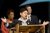 The Rev. Grace Cajiuat leads a liturgical version of the United Methodist Social Creed during a celebration of the creed's 100th anniversary at the 2008 General Conference. In the background are Bishop Beverly Shamana and Jim Winkler.