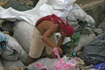 A man searches through bags of garbage for recyclables to resell in the Payatas landfill in Manila, Philippines. The island nation's capital city is one of the most densely populated places on earth.