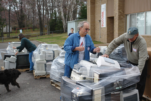 The Rev. Charlie West (center), pastor of Grace United Methodist Church in Marquette, Mich., collects electronic discards during the 2006 Earth Keeper Clean Sweep. A UMNS file photo by Greg Peterson.