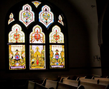 Stained-glass windows cast shadows on the empty pews inside Grace United Methodist Church.
