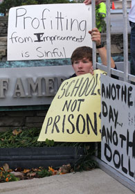 A young adult protests corporate profit from incarceration.