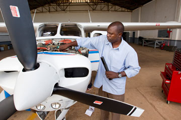 Missionary pilot and mechanic Gaston Ntambo readies the Wings of the Morning plane for its next flight. A UMNS photo by Mike DuBose.