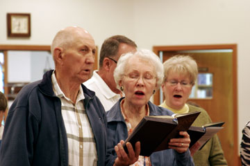 Robert and Faye Sundin praise God at Bowbells United Methodist Church. Behind them are Dean and Sally Verstrate. A UMNS photo by Jan Snider.