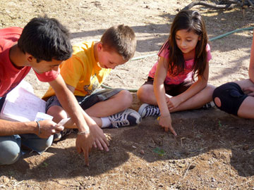 Students from the after-school garden class at Davis Elementary plant with André Luiz de Oliveira Domingues. Photo courtesy of Julie Diaz.
