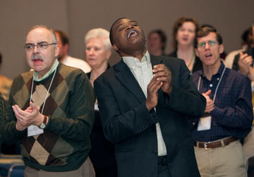 Mike Bella (left) and the Rev. Maidstone Mulenga join in worship during The United Methodist Church's pre-General Conference news briefing. A UMNS photo by Mike DuBose.