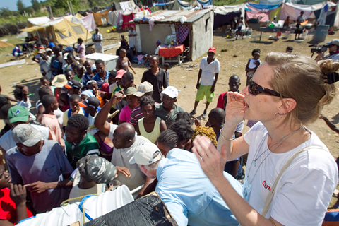 Melissa Crutchfield of the United Methodist Committee on Relief helps distribute water-treatment supplies to people living in a makeshift camp in Gresier, Haiti, in January 2010. UMNS file photos by Mike DuBose.