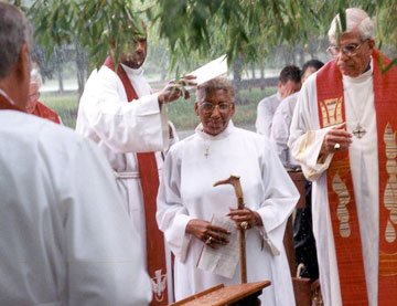 Alfred Johnson (left) tries to keep the rain out of the Rev. Violet L. Fisher's face during her service of consecration as a bishop in Somerset, N.J., in 2000. To her right is Bishop George W. Bashore. A UMNS photo by Dean Snyder.