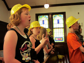 Singing while wearing hardhats goes with the theme of