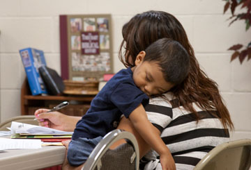 A DACA applicant cradles her son as she fills out the many pages of paperwork required by Immigration and Customs Enforcement.