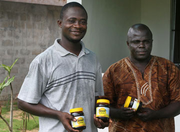 Duke Nyaeh and Ezekiel C. Freeman display their finished product, Liberian honey. Other sustainable products in Liberia include raising snails and using roots and leaves from the Moringa tree.