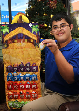 Store visitor, Andrew Donaldson, shows how to use a special holiday item offered by Cokesbury  a Fisher-Price Advent Calendar made of fabric.  Donaldson visits Cokesbury weekly through a community-based transition program.