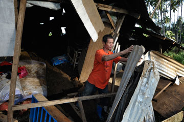 Armando Guniyon pulls apart the rubble of his home, damaged by floodwaters from Typhoon Bopha, in Cagayan de Oro, Mindanao, Philippines.
